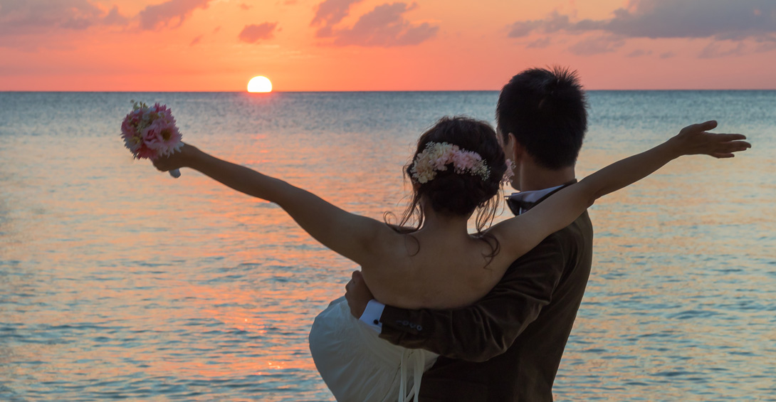 Groom carries bride on beach at sunset