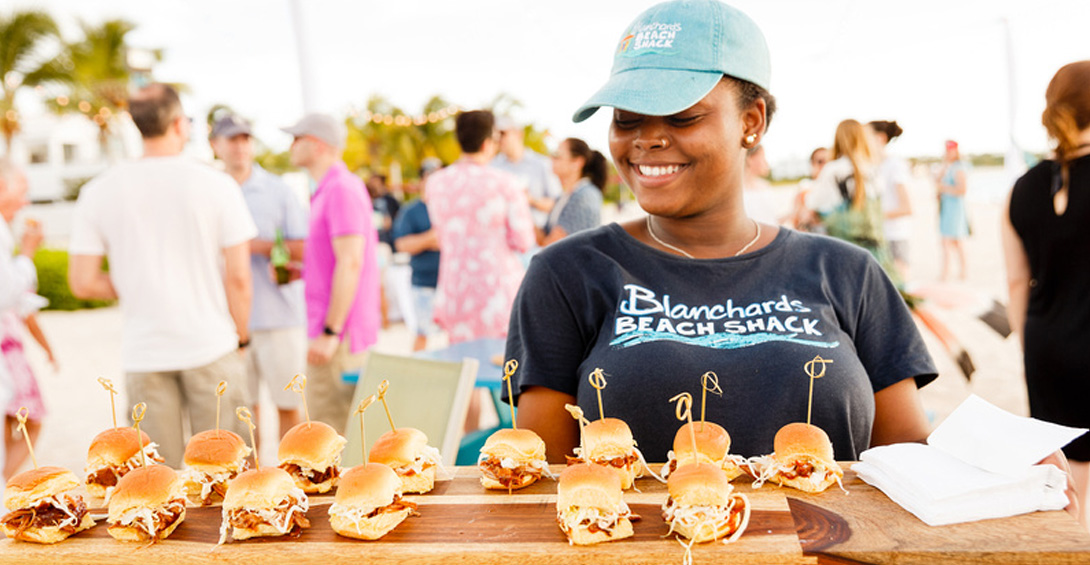 Server passes appetizers sliders on large wooden platter on the beach