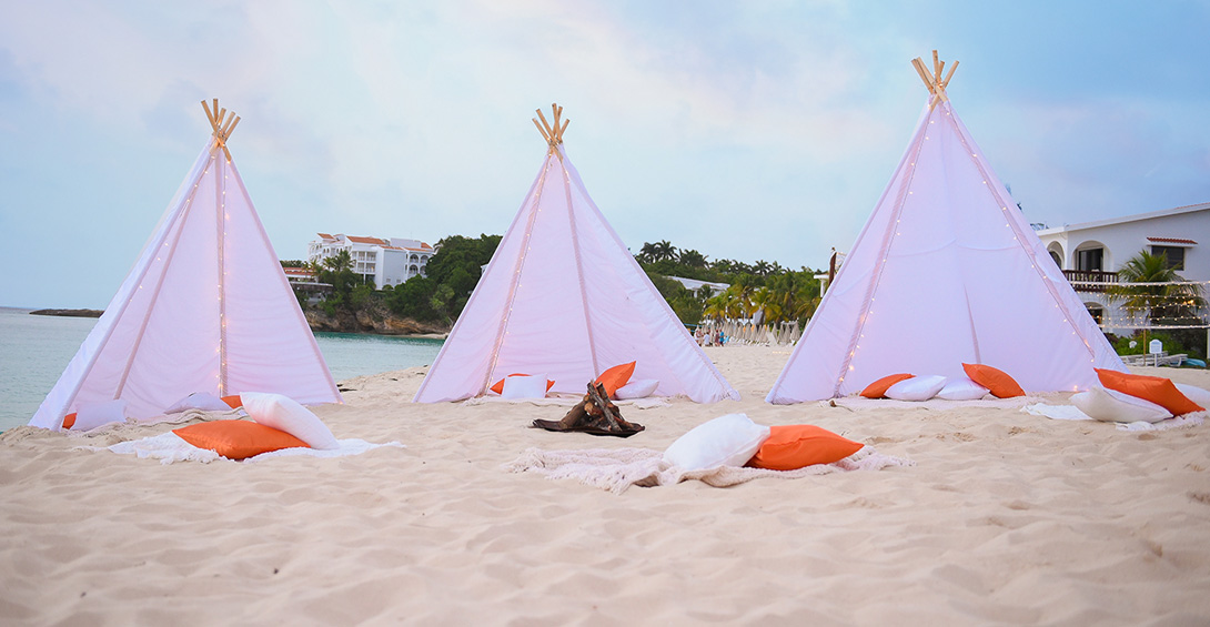 Tee pees set up on the beach around a bonfire at private event