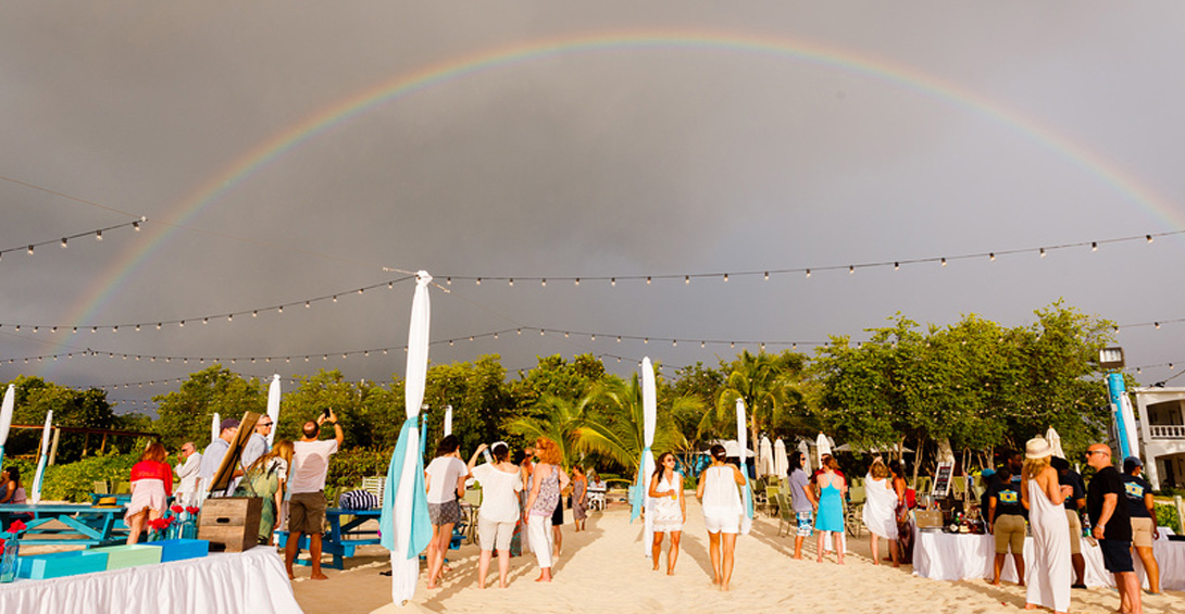 Event attendees admire rainbow in the sky above beach