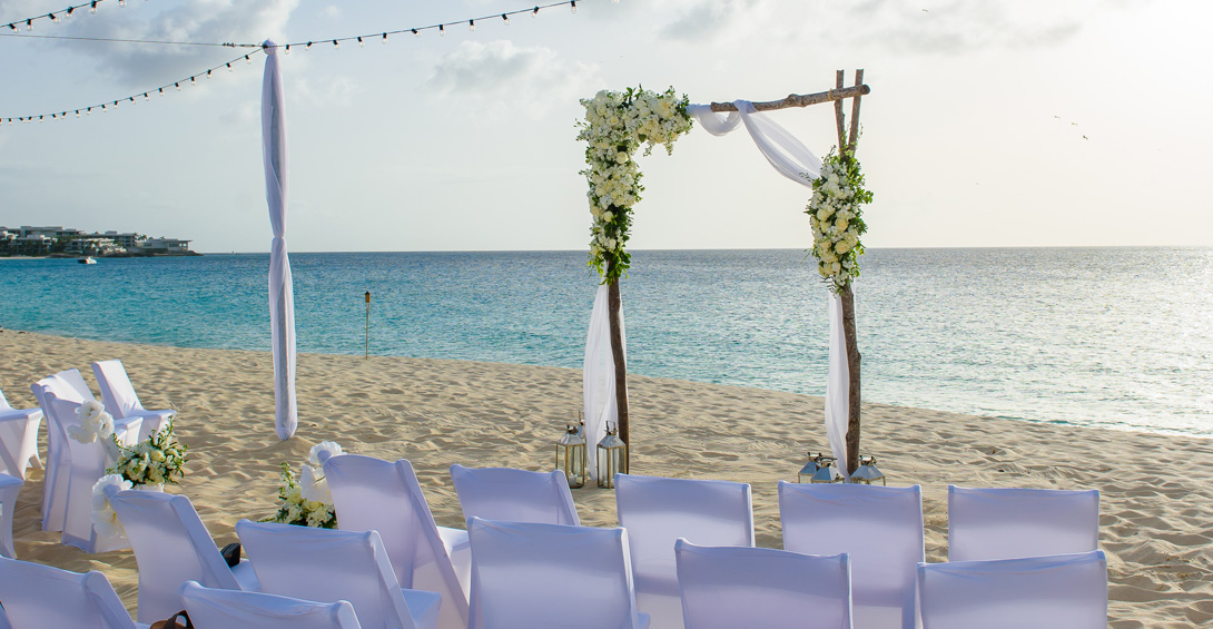 Beach wedding ceremony with simple alter of flowers and branches