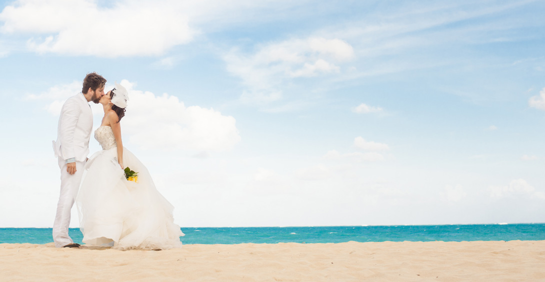 Bride and group kiss on white sand beach