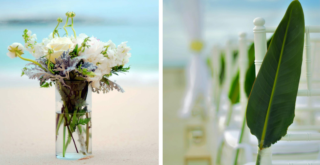 Flowers on vase on beach and palm leaf frond decoration at wedding