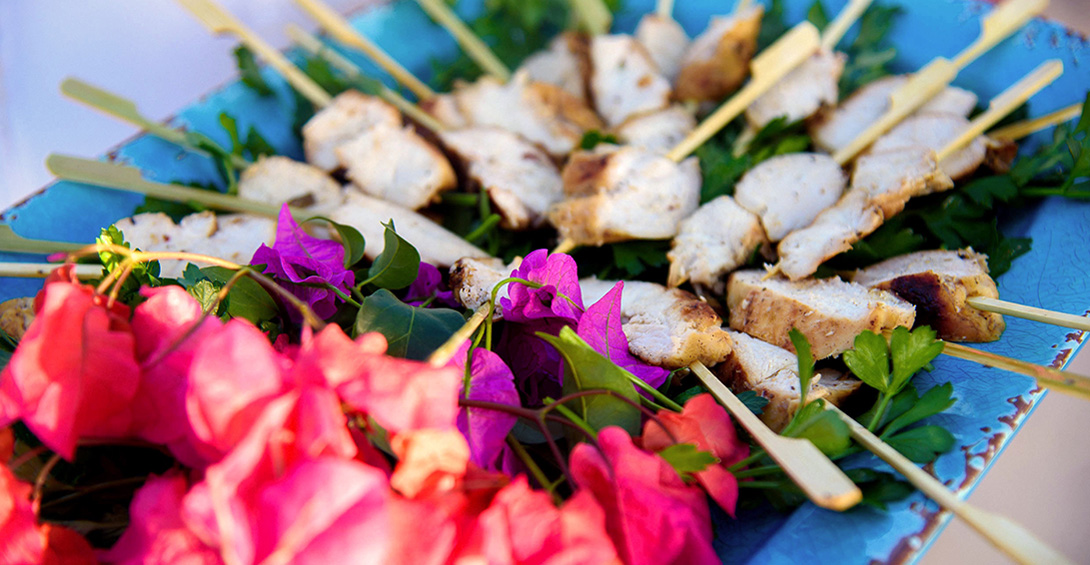 Chicken skewers served on blue platter with decorative tropical pink flowers