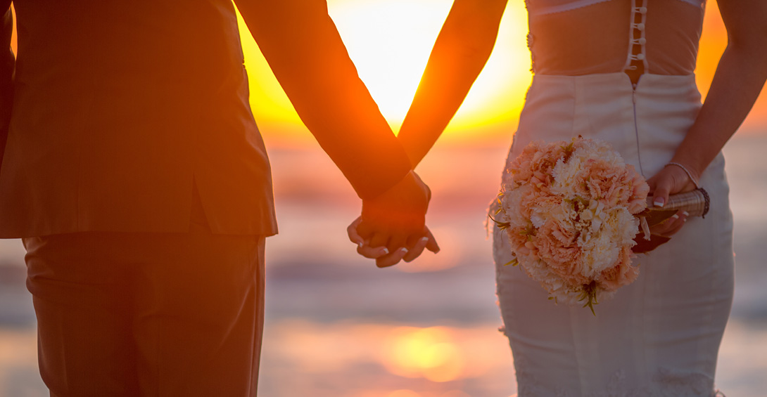 Bride and groom hold hands at sunset on beach