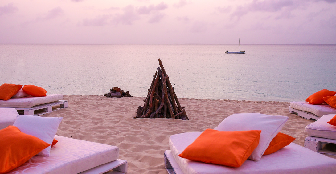 Bonfire on meads bay beach with cushions for seating at sunset and dusk