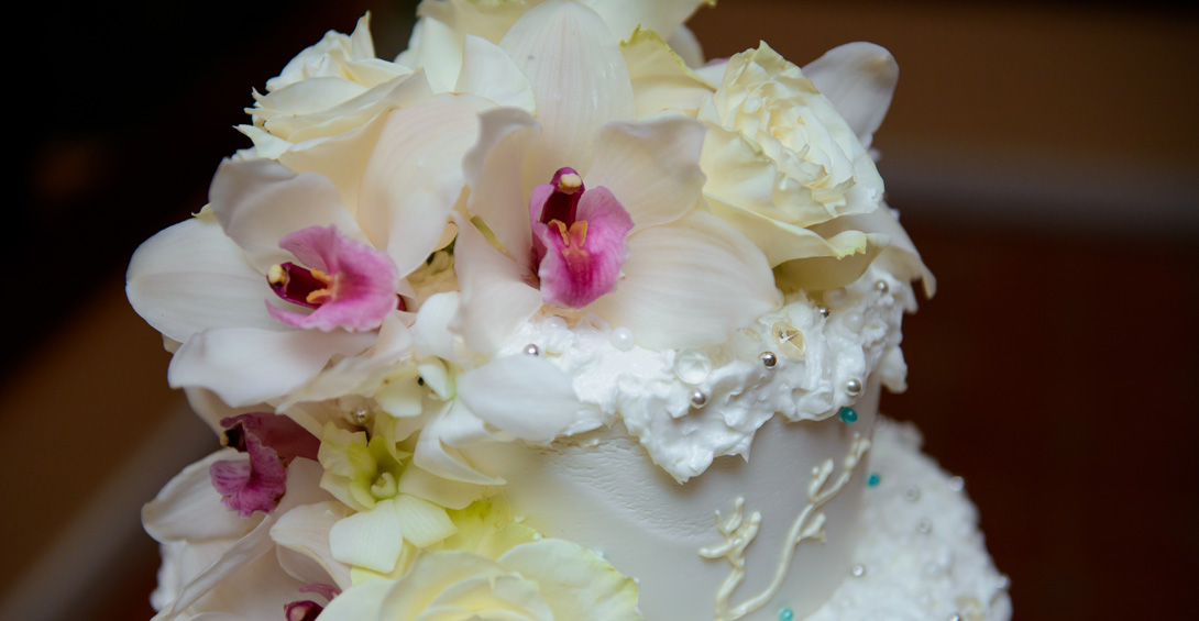 Wedding cake decorated with delicate flowers and coral piping