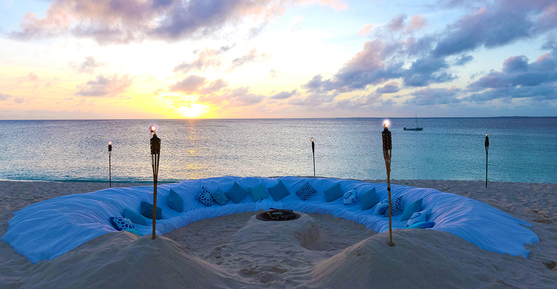 Sand couch on beach at sunset with tiki torches in front of Caribbean sea