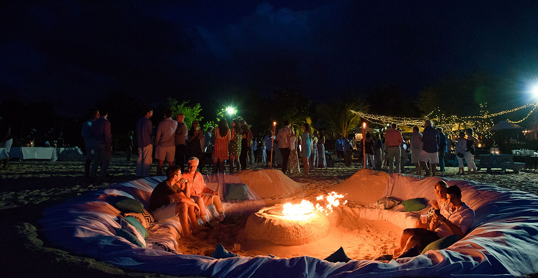 Event guests at beach party in Anguilla relaxing on sand couch around a bonfire