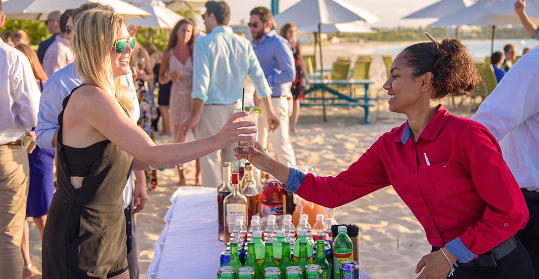 Blanchards bartender hands drink to guest at private bar on beach