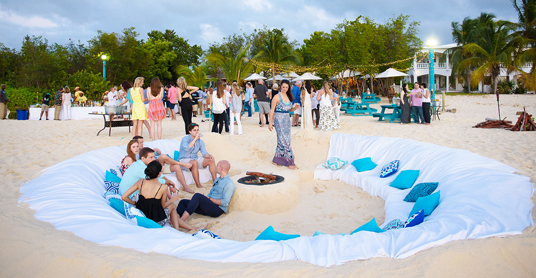 Corporate event guests sit on sand couch at beach party