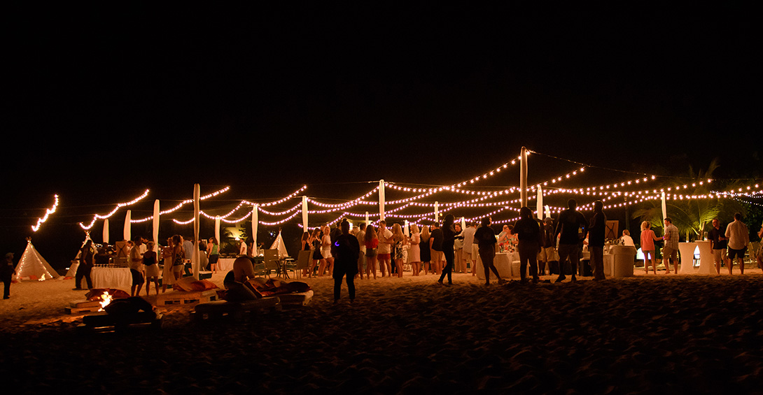 Twinkly lights glow in night sky above private party on beach in Anguilla