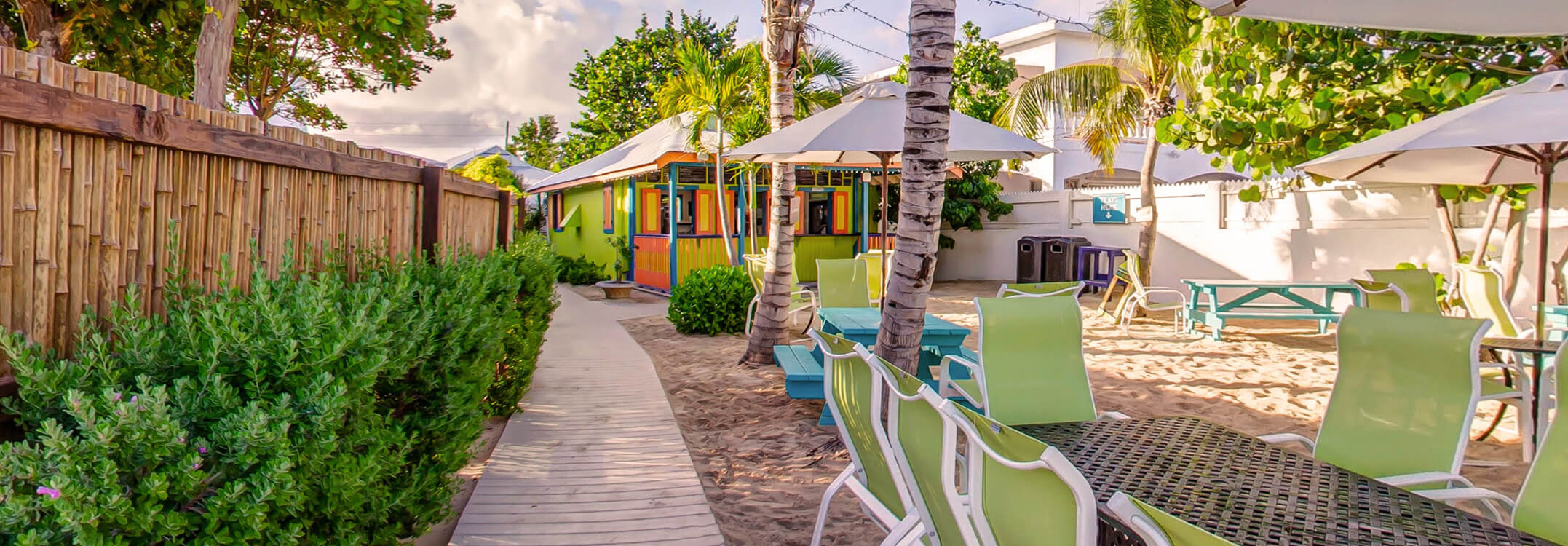 Path to colorful Beach Shack with seating on Anguilla beach shaded by umbrellas and palm trees