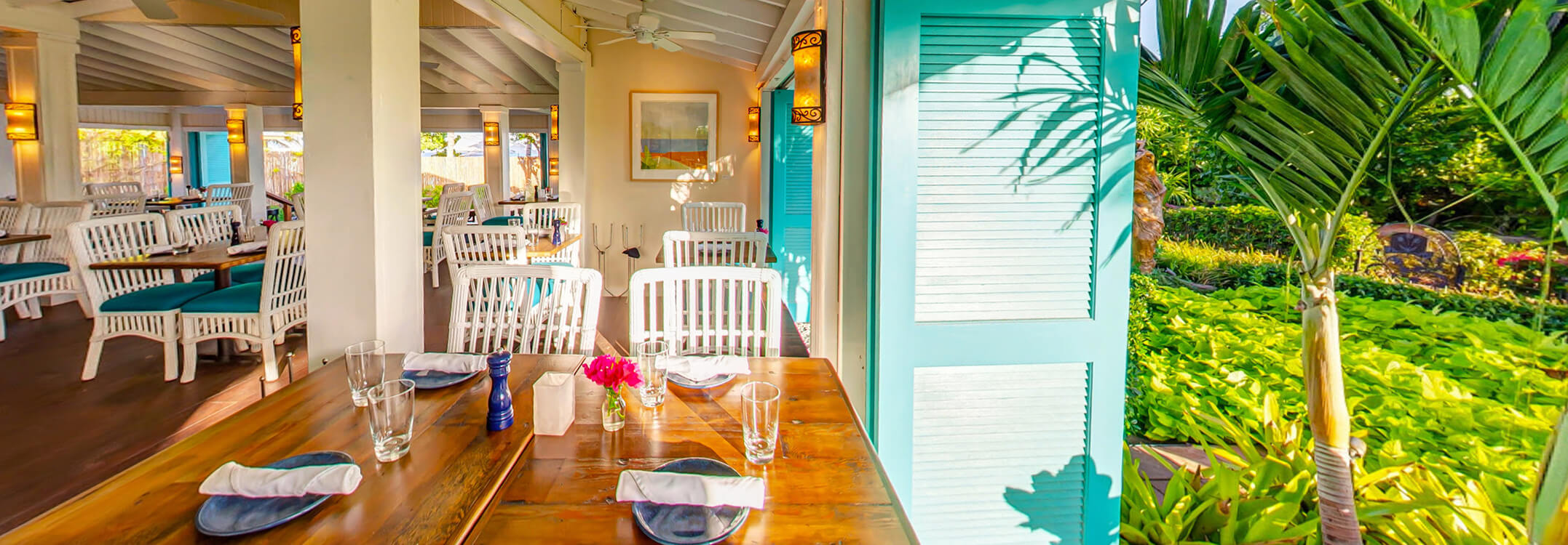 Open and airy Blanchards dining room with long teal shutters open to tropical garden