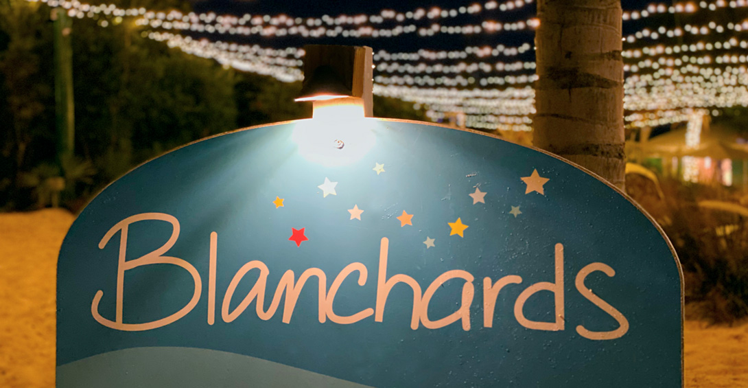 Blanchards sign on Meads Bay beach in front of strings of bistro lights glowing in the dark